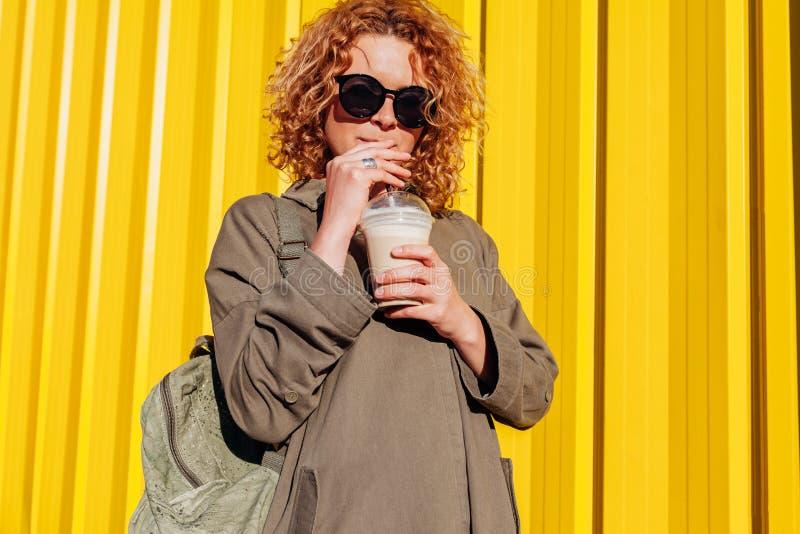 行家少妇用背包饮用的咖啡对黄色墙壁 太阳镜放松的时髦的夏天旅行家 免版税库存图片