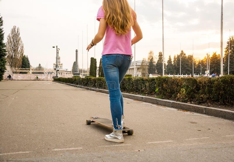 行家少年女孩的腿乘坐在aban的一个滑板 库存照片