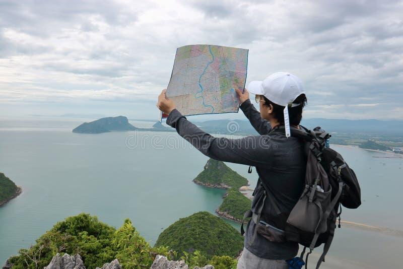 行家年轻亚裔人广角射击有站立在石头和探索的地图的背包的在山 图库摄影