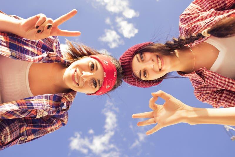 行家成套装备的两个深色的十几岁的女孩朋友(牛仔裤短缺, keds、格子花呢上衣,帽子)有在户外公园的一个滑板的 免版税库存图片