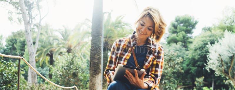 行家手数字片剂的人藏品有屏幕的,少女在计算机上的微笑读书在背景自然公园棕榈 免版税库存图片