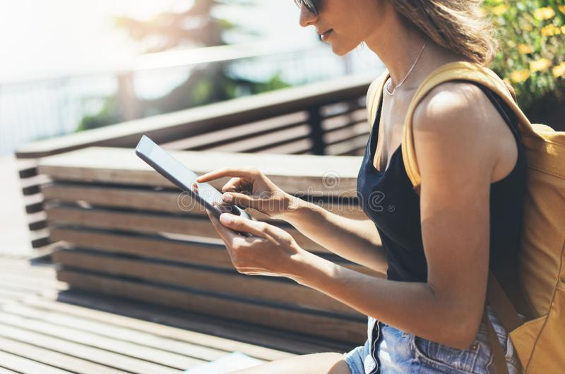 行家手数字片剂的人藏品有黑屏的,在计算机上的女孩照片在背景自然夏天公园 免版税库存图片