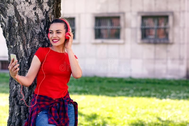 行家时髦的美丽的女孩听到音乐的,手机, 免版税图库摄影