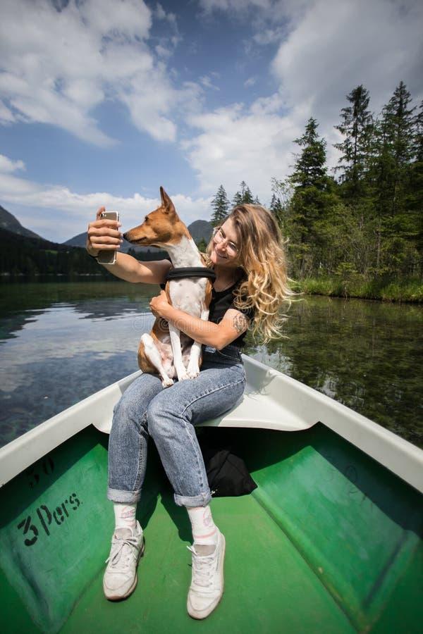 行家有最好的朋友宠物的旅行妇女在小船 库存照片