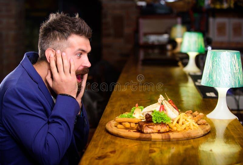 行家正装坐在酒吧柜台 人接受了与油煎的土豆的膳食炸鱼排肉 可口膳食 享受膳食 库存照片