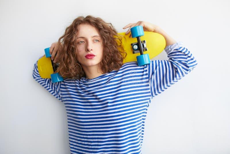 行家的年轻深色的女孩给拿着五颜六色的滑板穿衣 库存照片
