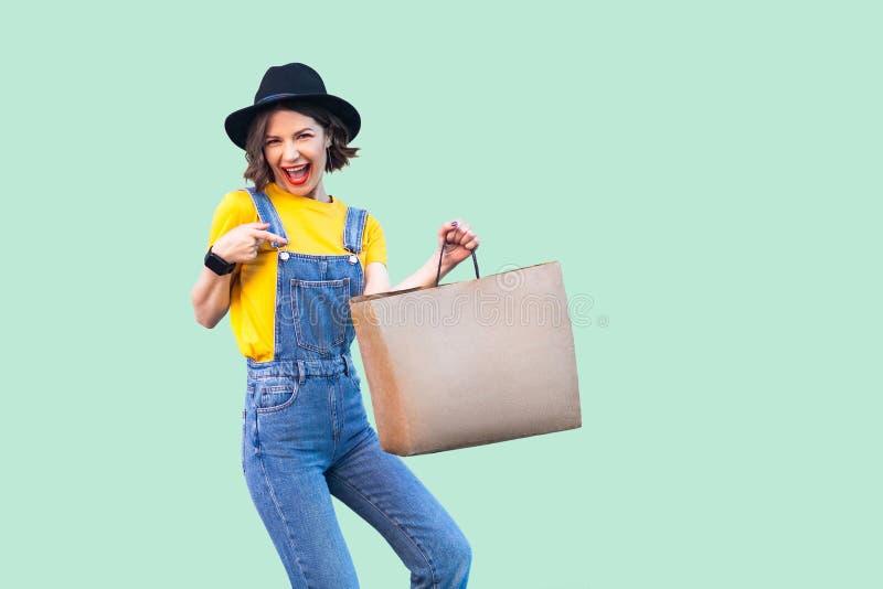 行家穿戴在牛仔布总体和黑帽会议身分和指向手指的乐趣美丽的少女到购物带来与 库存照片