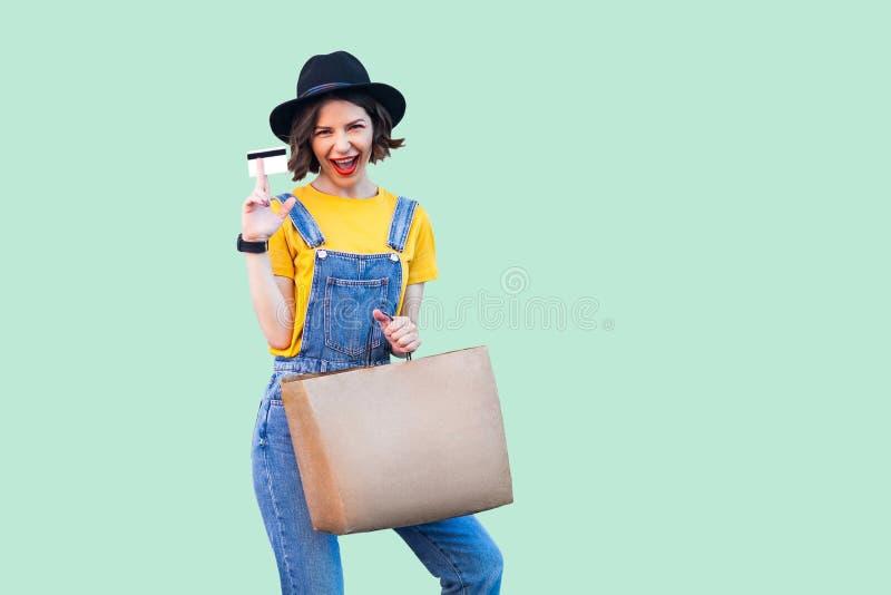 行家穿戴的乐趣美丽的少女在牛仔布总体和黑帽会议身分,拿着万一银行卡和购物带来,开放 免版税库存照片