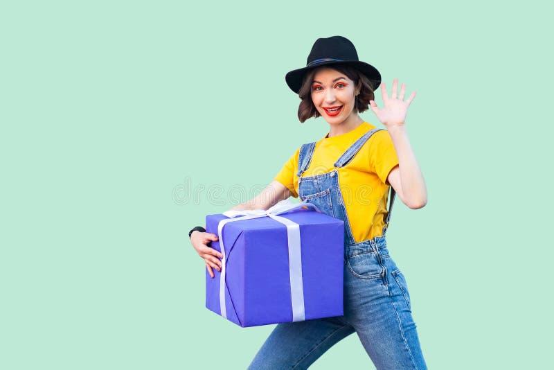 行家穿戴的快乐的愉快的少女在牛仔布总体和黑帽会议身分和设法拿着巨型大重的礼物盒和 库存照片