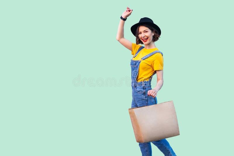 行家穿戴的快乐的美丽的少女在牛仔布总体和黑帽会议藏品商店袋子暴牙的微笑,庆祝伟大 免版税库存照片