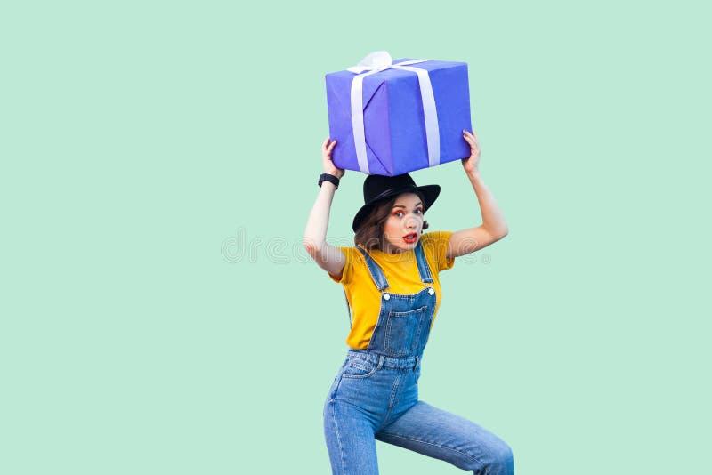行家穿戴的惊奇的滑稽的少女在牛仔布总体和黑帽会议身分和举行在头巨型大重的礼物盒下 免版税图库摄影