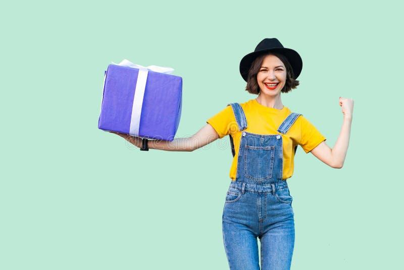 行家穿戴的愉快的可爱的少女在牛仔布总体和黑帽会议身分和拿着有暴牙的大重的礼物盒 免版税库存图片