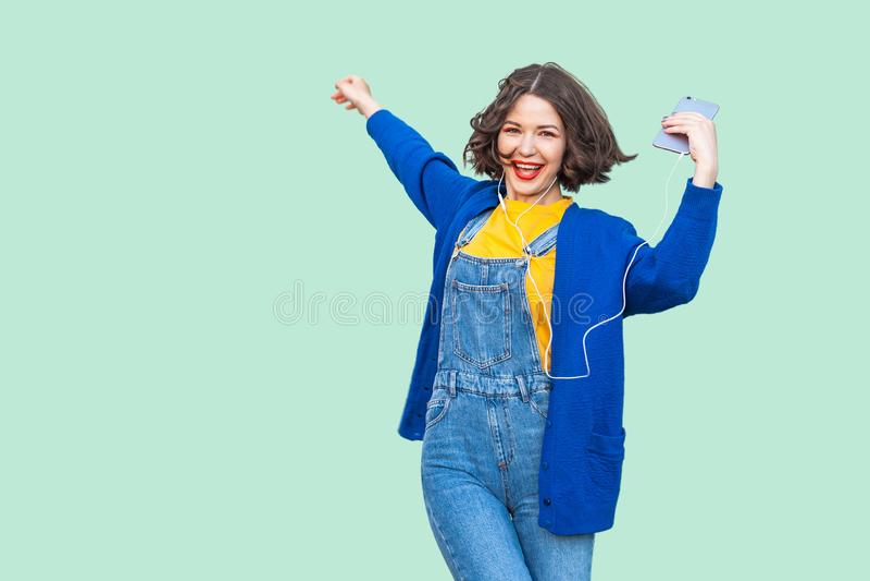 行家穿戴的美丽的快乐的年轻妇女在站立牛仔布的总体,举行电话和听的喜爱的音乐与 免版税库存图片