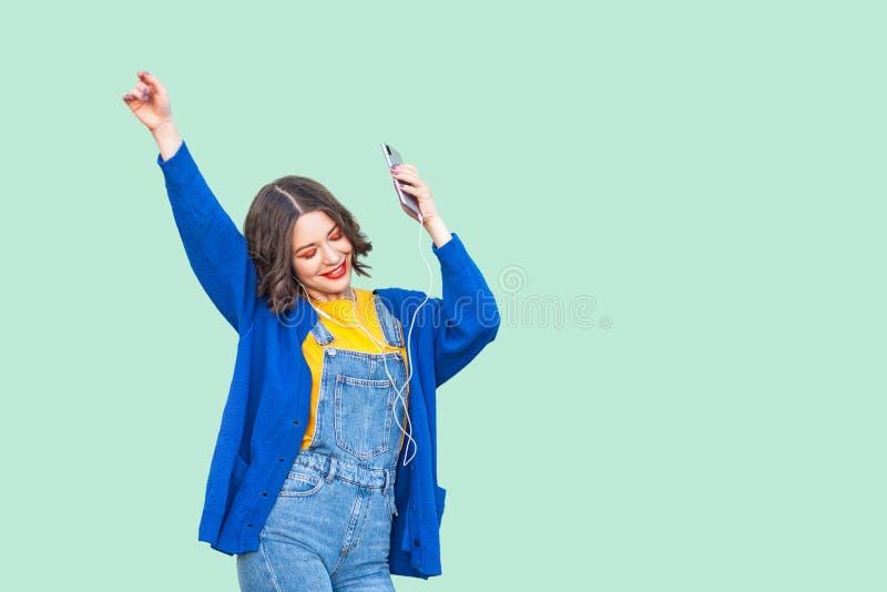 行家穿戴的美丽的正面年轻成人女孩在站立牛仔布的总体,举行电话和听的喜爱的音乐与 免版税库存图片