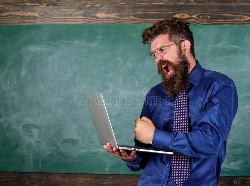 行家老师积极与膝上型计算机发狂关于慢速互联网连接 老师有胡子的人现代膝上型计算机 库存图片