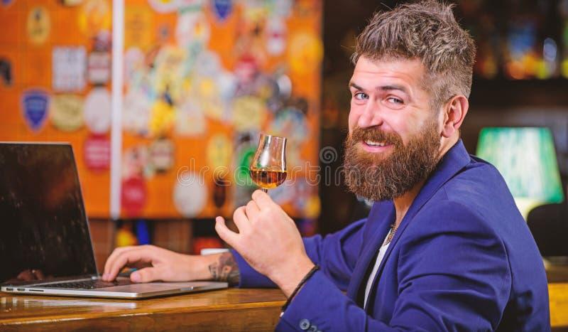 行家自由职业者工作网上饮用的科涅克白兰地 人有胡子的商人酒吧柜台膝上型计算机科涅克白兰地 宜人放松 免版税库存照片