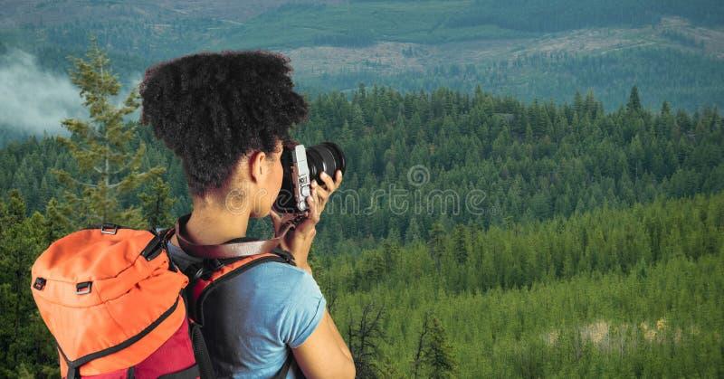 行家运载的背包和拍摄与照相机,当站立在峭壁时 库存照片