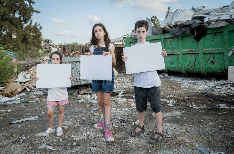 行星保存 拿着标志的小孩站立在巨大的废品旧货栈 免版税图库摄影