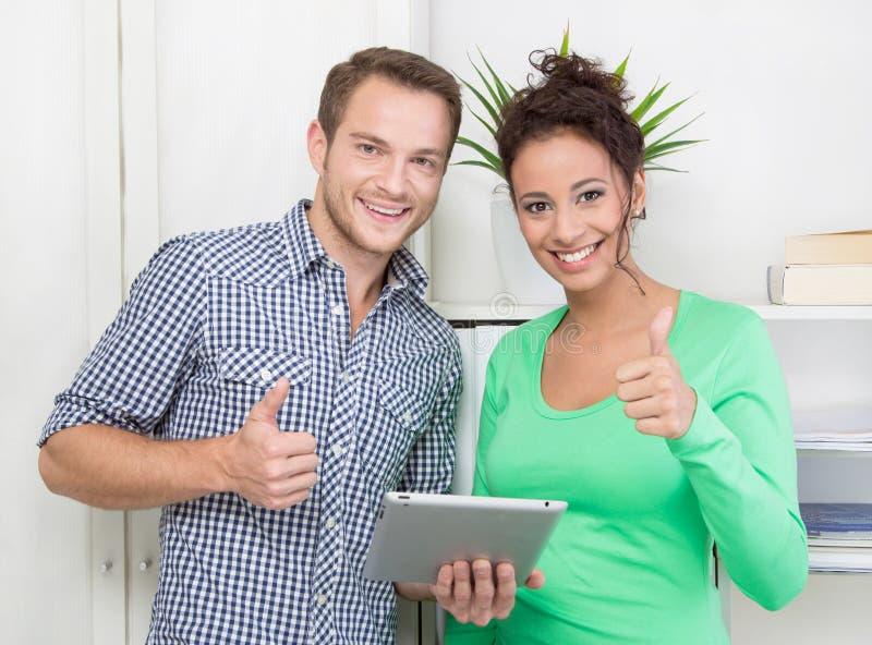 行显示与赞许和片剂个人计算机的同事 免版税库存照片
