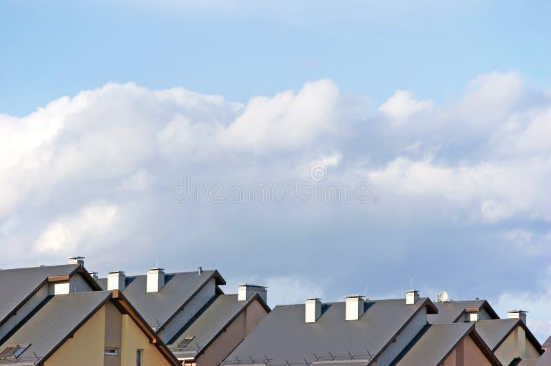 行格住宅屋顶、公寓房屋顶全景和明亮的夏天云彩晴朗的cloudscape 免版税库存图片