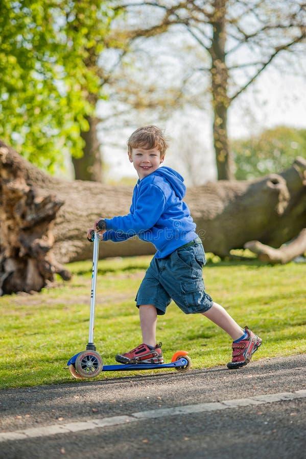 滑行车的微笑的年轻男孩 免版税图库摄影