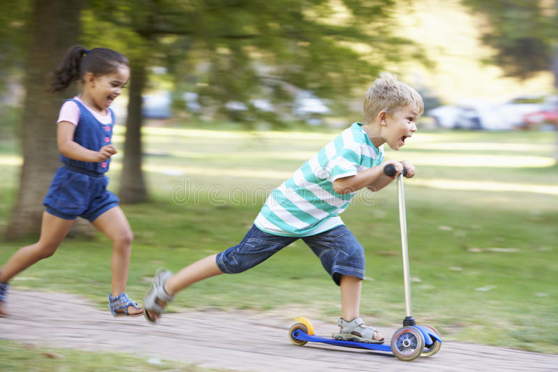 滑行车的年轻男孩在有姐妹的公园 库存图片