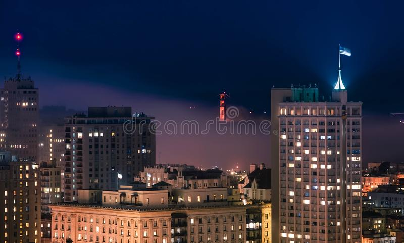街市圣Fransisco大厦的美丽的射击与金门桥的在夜间 免版税库存照片