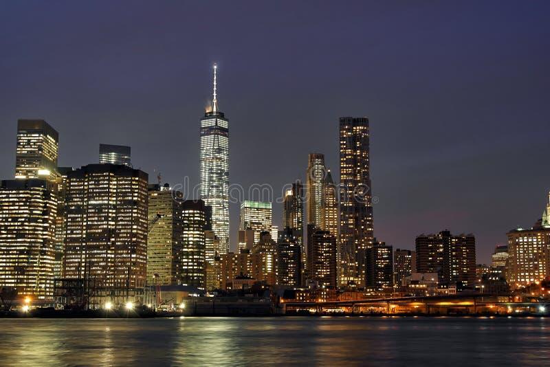 街市曼哈顿在与新的世界贸易中心和East河的晚上 免版税库存图片