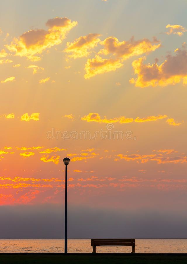 街灯和长凳在美好的明亮的红色日落前面 图库摄影