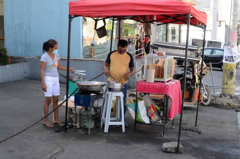 街边食物贩子在市区人行道上做饭,即使看不到顾客 库存照片
