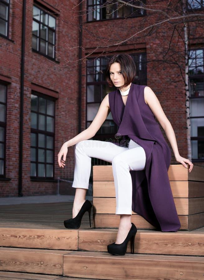 街道一个美丽的少妇的时尚画象紫色礼服和白色裤子的 免版税库存照片