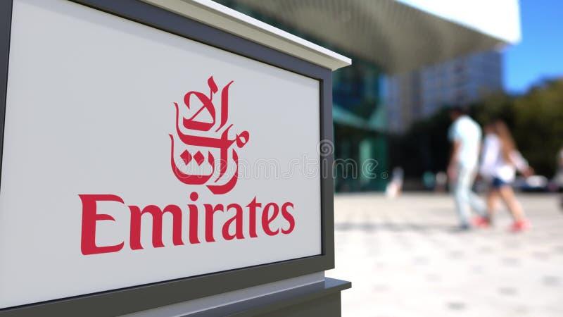 街道与阿联酋国际航空商标的标志板 被弄脏的办公室中心和走的人背景 社论3D 免版税库存图片