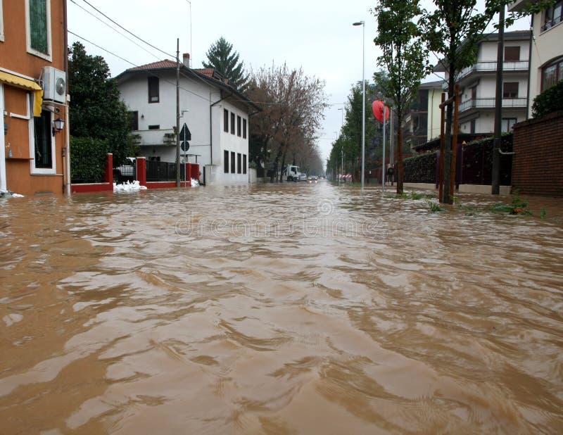街道充斥了与泥和残骸在一次洪水期间在镇里 免版税库存照片
