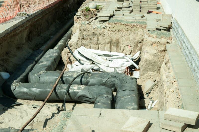 街道分区供暖与老管子的地面挖掘末端替换的系统管道重建站点有新的 库存照片