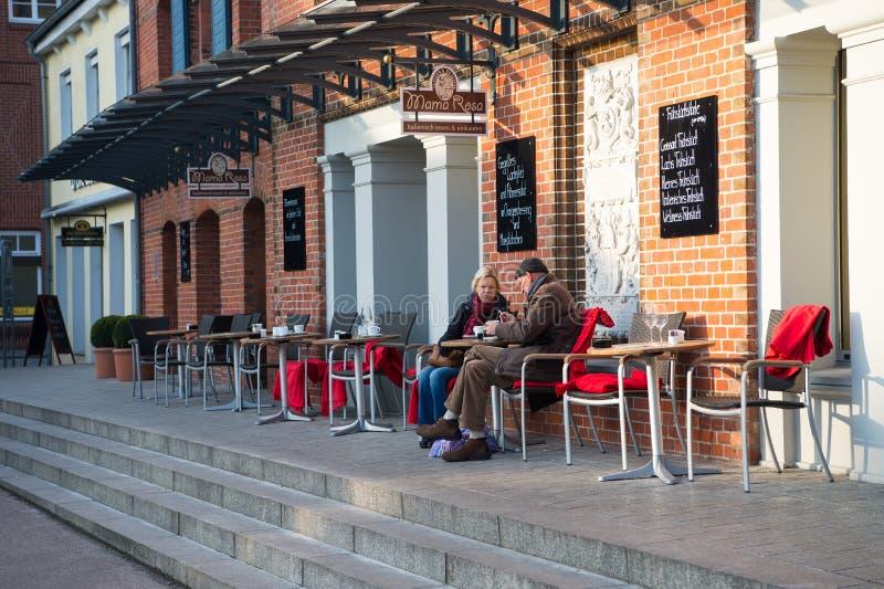 街道咖啡馆用老夫妇饮用的咖啡在桌上户外 免版税库存照片