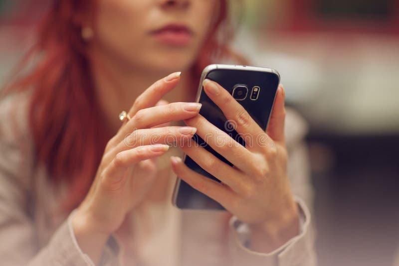 街道咖啡馆的年轻美丽的妇女,是繁忙的与她的手机,关闭在拿着手机的手 库存图片