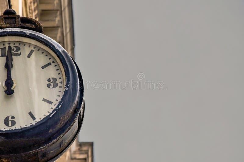 街道在一个老大厦的葡萄酒时钟在灰色天空背景 零件或减速火箭的手表拨号盘的一半  免版税图库摄影