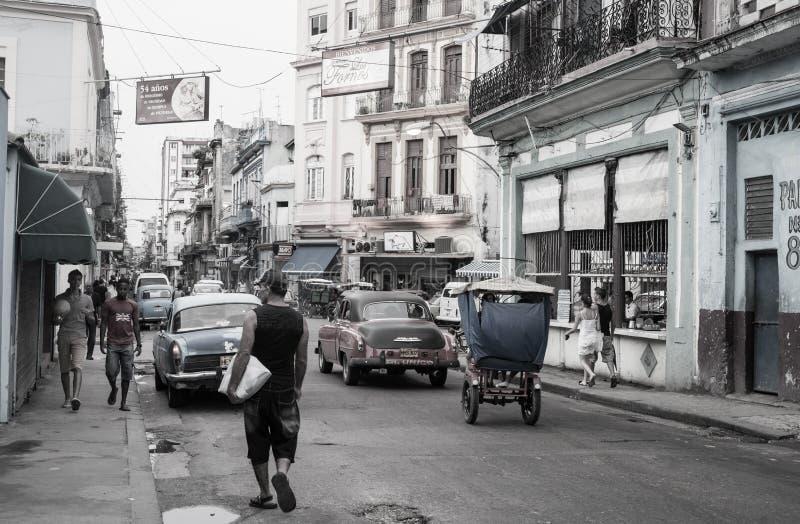 街道在有来回走的人,经典美国车和老被毁坏的大厦的哈瓦那 库存图片