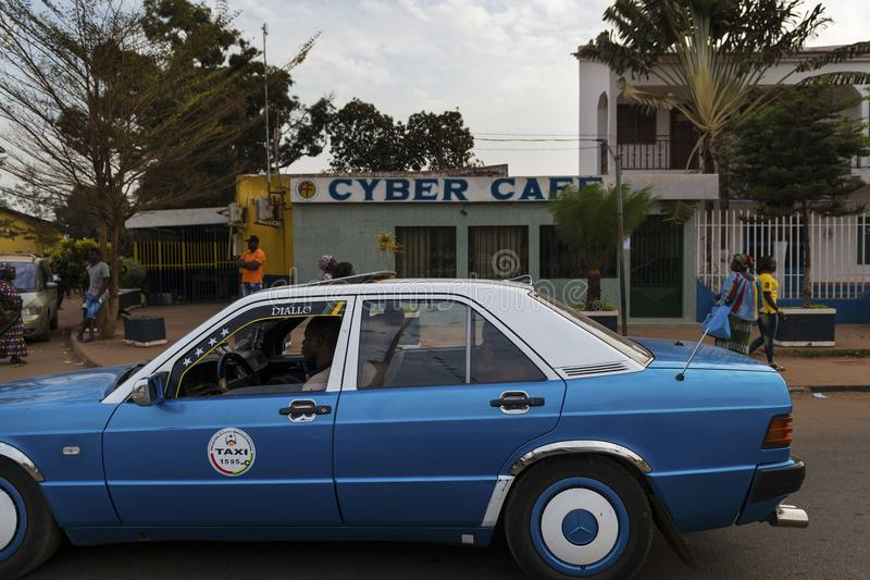 街道场面在市有通过在一个网络咖啡馆前面的出租汽车和人的比绍,在几内亚比绍 图库摄影