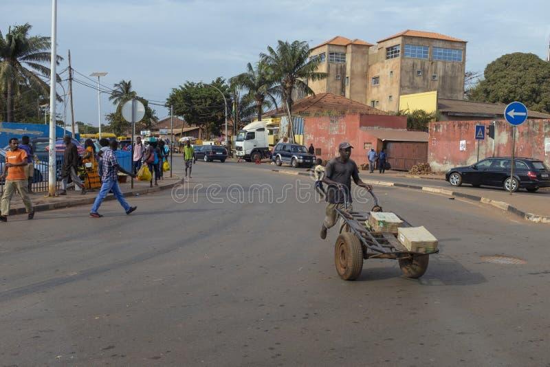 街道场面在比绍的有穿过街道的人的在Bandim市场附近,在几内亚比绍 库存图片