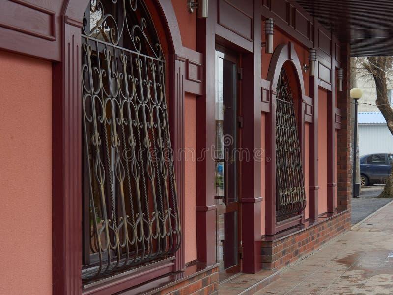 街道城市建筑学公共频道播送胡同边路污迹玻璃窗红色门的树 库存照片