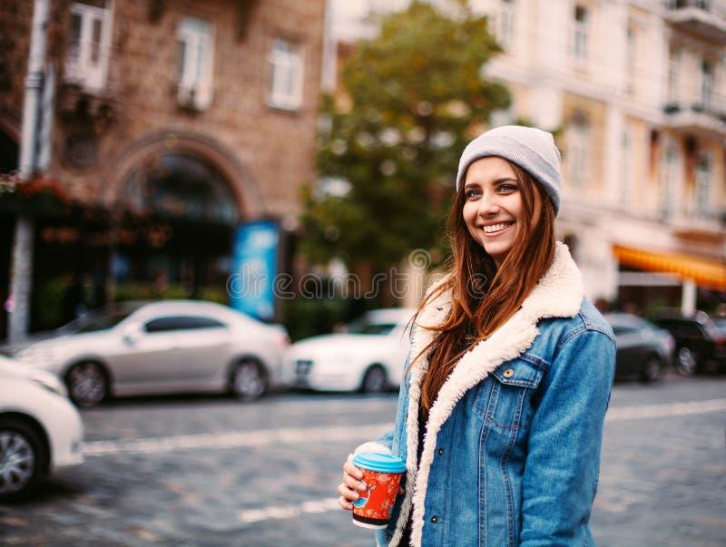 街道时尚的概念 年轻时髦的女学生 穿戴在一个灰色帽子,牛仔布夹克拿着咖啡并且笑 好moo 图库摄影