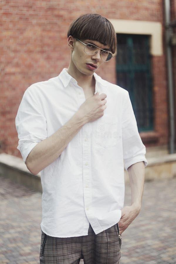 街道样式时尚概念的年轻行家人 人穿戴时髦的眼镜的白色衬衫 式样人 库存图片