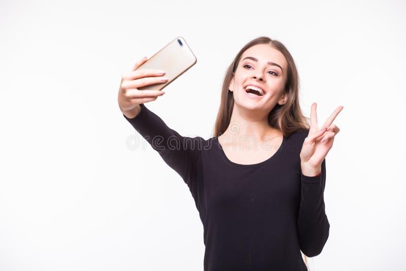 街道样式的华美的少妇给采取与手机的selfie穿衣被隔绝在白色背景 库存照片