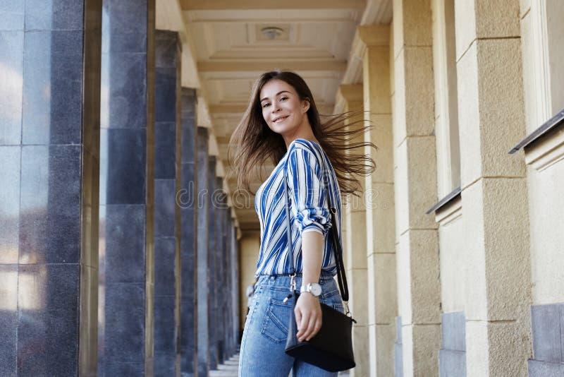 街道样式美女户外画象  方式微笑的妇女 她佩带的印刷品衬衣,牛仔裤,袋子 生活方式 免版税库存图片