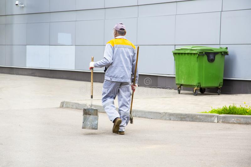 街道清扫车工作者清洁城市街道 免版税库存照片
