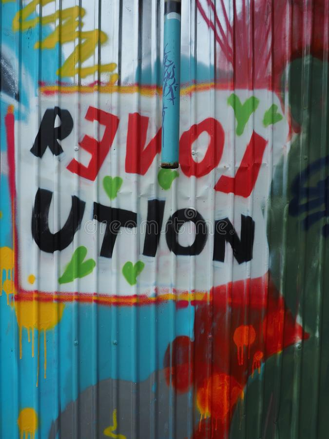 街道画在波纹状的篱芭的爱革命 图库摄影