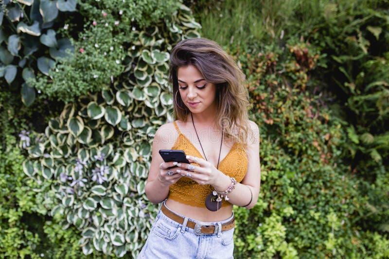 街道的年轻白肤金发的美女使用手机和微笑 生活方式户外 夏令时,绿色背景 库存图片