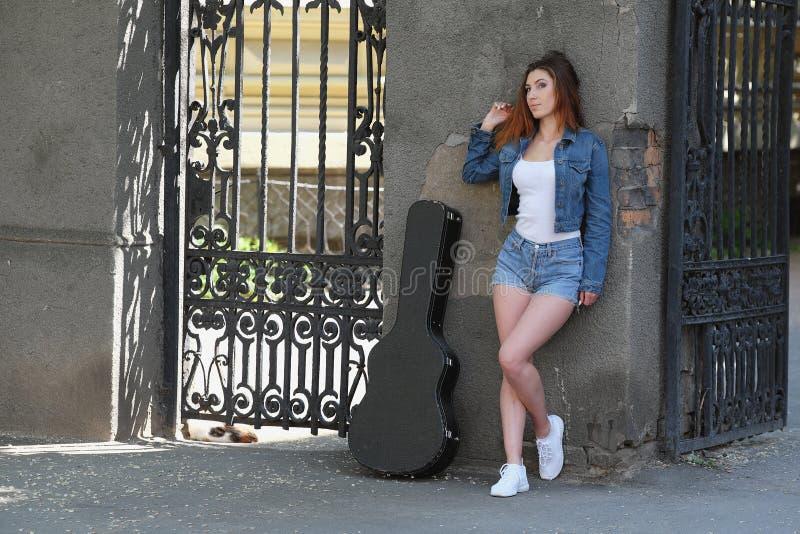 街道的红头发人美丽的女孩有在案件的一把吉他的 免版税库存照片