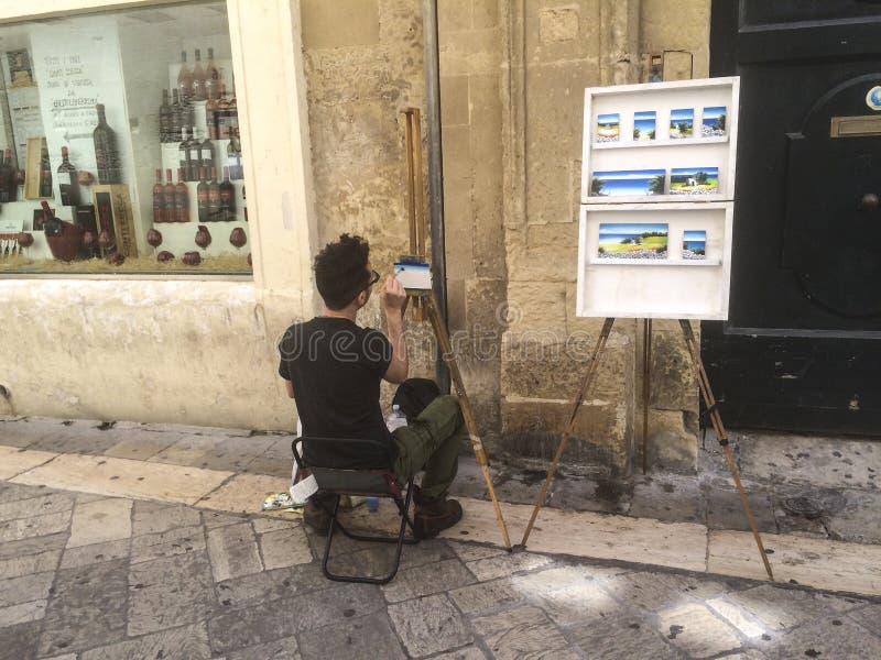 街道艺术家,在莱切普利亚意大利街道的油漆图片  免版税库存图片